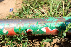 Tube swing with large layers of red, white and green paint Royalty Free Stock Image
