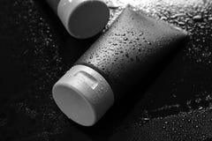Tube on wet black surface. Men`s cosmetic product. Tube on wet black surface, space for design. Men`s cosmetic product royalty free stock images