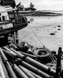 Tube and wheel at sea with low tide time. Black and white stock photo