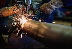 Tubería de acero del corte del trabajador con el soplete cortador a de la soldadura al acetileno Imagen de archivo libre de regalías