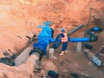 Tubería principal de la fuente del suministro de agua Personal técnico en el chaleco reflexivo subterráneo imagen de archivo libre de regalías