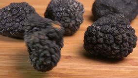 Tuber of black truffle rolls on the table. Tuber of black truffle rolls on the wooden table stock video footage