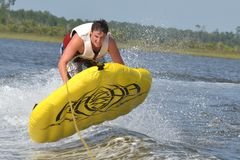Tuber Launching Off of Boat Wake. Teenage boy launching off boat wake in inner tube with a great look of effort on his face Royalty Free Stock Images