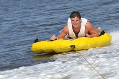 Tuber Sliding Outside of Boat Wake. Teenage sliding across boat wake in inner tube with a great look of effort on his face. Getting ready to cross wake for his Royalty Free Stock Images
