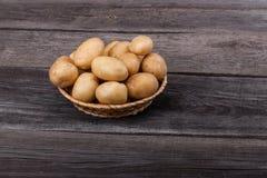 Tubercule de pomme de terre dans le panier en osier dessus sur la table en bois Image stock