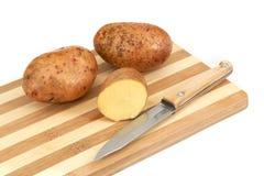 tubers för potatis för brädecutting liggande rå Arkivbild