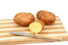 tubers för potatis för brädecutting liggande rå Royaltyfri Fotografi