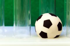 Tubes à essai rayés médicaux et un ballon de football de souvenir sur un fond vert Argent de concept et sports, médecine et footb Photo stock