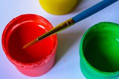 Tubes with acrylic or oil paint and brush over colorful artist`s palette, selective focus. stock photos