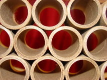 Tubes of cardboard with red background stock images