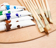 Tubes of colorful paint and paint brush Stock Photos