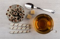 Tubes with cream in glass, tea, sugar and teaspoon. Tubes with cream in transparent glass, cup of tea, lumpy sugar and teaspoon on wooden table. Top view Stock Image