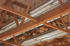 Tubes of an HVAC with roof with wooden beams in the new factory Stock Photos