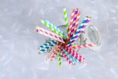 tubes jetables colorés de papier rayé dans un pot sur un fond gris Photos libres de droits