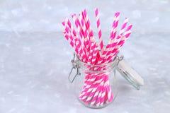 Tubes jetables roses de papier rayé dans un pot sur un fond gris Images stock