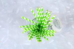 Tubes jetables verts de papier rayé dans un pot sur un fond gris Images libres de droits