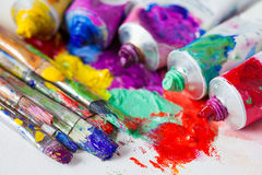 Tubes of multicolor oil paint and artist paintbrushes on canvas. Closeup royalty free stock image