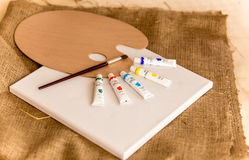 Tubes with oil paints and wooden pallet on table at art classroom. Tubes with oil paints and wooden pallet lying on table at art classroom stock photos