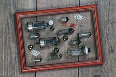 Tubes par radio et composants électroniques dans un cadre sur une étiquette en bois Photo stock