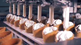 Tubes are pumping creamy substance into lines of wafer cones. 4K stock video footage