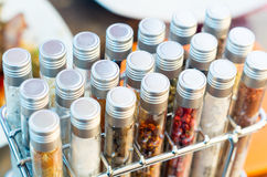 Tubes of spices placed inside metal rack and some Royalty Free Stock Photos