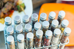 Tubes of spices placed inside metal rack and some Royalty Free Stock Photography