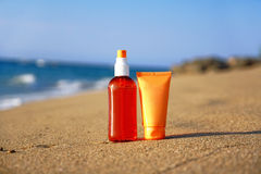 Tubes with sun protection on beach Stock Photos