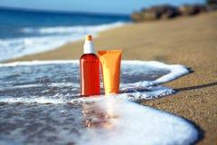 Tubes with sun protection on beach of Atlantic oce Stock Photos