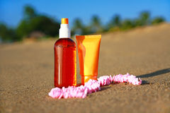 Tubes with sunblock and bread on sand on beach Stock Photography