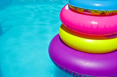 Tubes in swimming pool. Inflatable colorful tubes in swimming pool Stock Photo