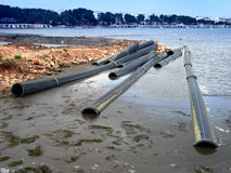 Tubes in the water. Industrial tubes thrown to the contaminated water Royalty Free Stock Photos