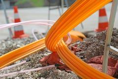 Tubi arancio per le fibre ottiche in una costruzione di strade di grande città Fotografia Stock Libera da Diritti