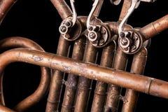 Tubi bronzei dell'annata, valvola, corno francese degli elementi meccanici chiave, fondo nero Buon modello, strumento di musica r immagini stock libere da diritti