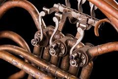 Tubi bronzei dell'annata, valvola, corno francese degli elementi meccanici chiave, fondo nero Buon modello, strumento di musica r immagini stock