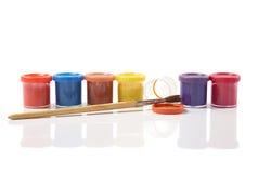 Tubi con una vernice su priorità bassa bianca Fotografie Stock