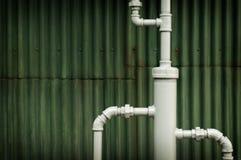 Tubi degli impianti idrici davanti al fondo di lerciume Immagine Stock