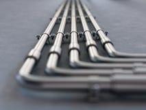 Tubi del metallo montati su una parete Fotografia Stock