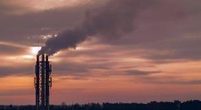 tubi di fumo al tramonto, inquinamento ambientale fotografia stock