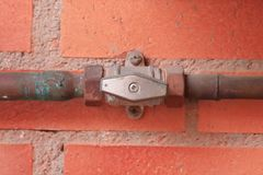 Tubi di gas e una valvola contro un muro di mattoni rosso fotografia stock libera da diritti