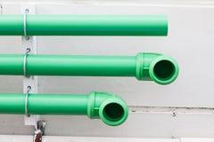 Tubi verdi sulla parete del cemento Fotografia Stock Libera da Diritti