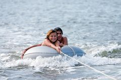 Tubing. Man and girl on tube in water being towed by boat Royalty Free Stock Photos