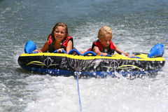 Tubing on the Lake. Two children enjoying a fun ride on the lake Royalty Free Stock Photo