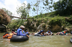 Tubing. Travelers enjoy a trip on the river water Oyo, in Gunungkidul, Indonesia Royalty Free Stock Images