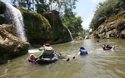 Tubing. Travelers enjoy a trip on the river water Oyo, in Gunungkidul, Indonesia Royalty Free Stock Photography