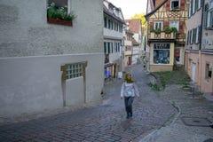 TUBINGEN/GERMANY- 30-ОЕ ИЮЛЯ 2019: Мусульманская маленькая девочка идя на путь около славных старых полу-timbered домов fachwerk стоковое фото rf