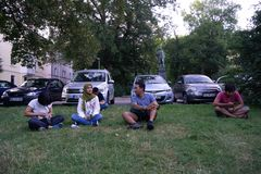 TUBINGEN/GERMANY-JULY 31 2018年:很多个亚裔游人坐草坪,在停车场附近,互相谈话 免版税库存图片