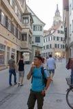 TUBINGEN/GERMANY-JULY 31 2018: en manlig turist från asia tycker om glass runt om tubingen den fot- staden bredvid honom där royaltyfri bild