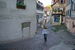 TUBINGEN/GERMANY-JULY 30 2019: A Moslem young girl walking on the path near Nice old half-timbered fachwerk houses royalty free stock photo