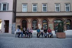 TUBINGEN/GERMANY-JULY 31 2018: some Asian Muslim tourists are sitting on a bench near the pedestrian street around the city of stock photography