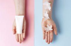 Tubka z śmietanką w żeńskiej ręce i białych kwiatach na tle błękita i menchii, odgórny widok, pojęcie naturalni kosmetyki fotografia royalty free